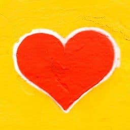 A drawing of a red heart on a yellow background.